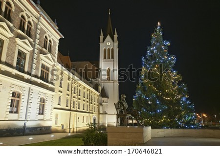 Christmas tree and church tower at night, Keszthely, Hungary - stock photo