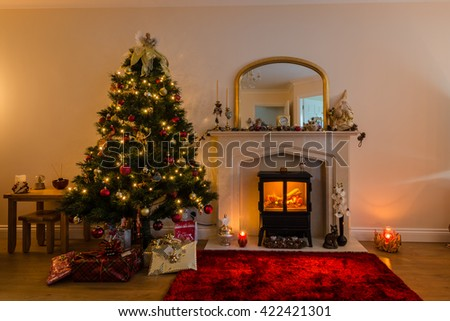 Christmas Tree and Fireplace / Warm glow of Christmas lights and a log burner in festive decoration - stock photo