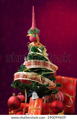Christmas tree and gift boxes, red background at Christmas stars - stock photo