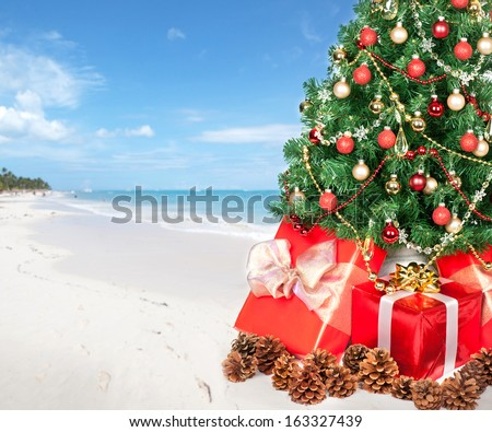 Christmas tree and gifts over beach background - stock photo
