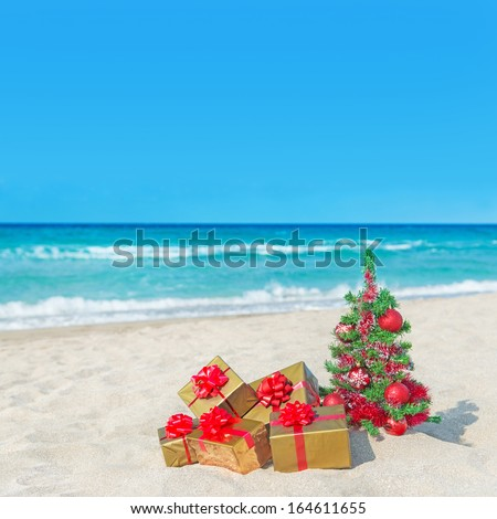 Christmas tree and golden gift boxes with big red bow on the sea sandy beach. Christmas vacation concept. - stock photo