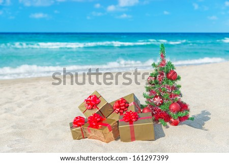 Christmas tree and golden gift with big red bow on the sea sandy beach. Christmas vacation concept. - stock photo