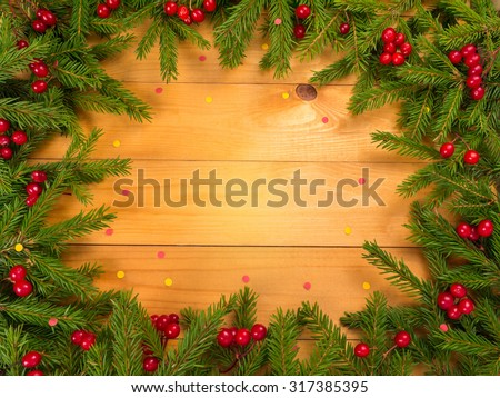 Christmas tree and red berries frame on the wooden planks background sprinkled with red and yellow confetti