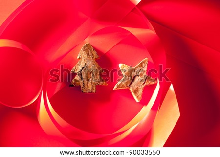 Christmas tree and star of tree bark on red background and ribbon