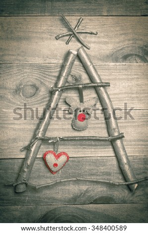 Christmas tree arranged from sticks, twigs, driftwood on wooden background. Handmade red and green heart and reindeer made from felt hanging on tree. Craft. - stock photo