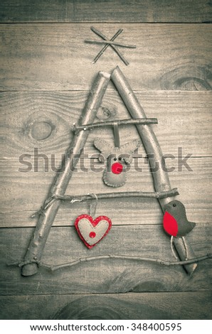 Christmas tree arranged from sticks, twigs, driftwood on wooden background. Handmade red and green heart, Rudolf reindeer and robin made from felt hanging on tree. Craft. - stock photo