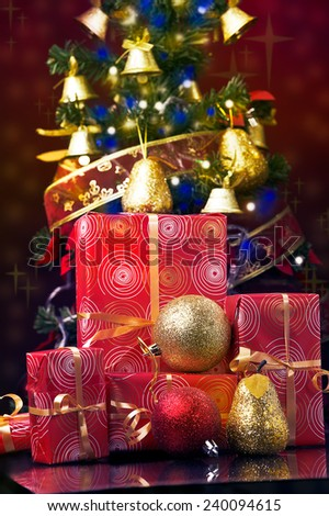 Christmas tree at the background and Christmas gifts at the front  - stock photo