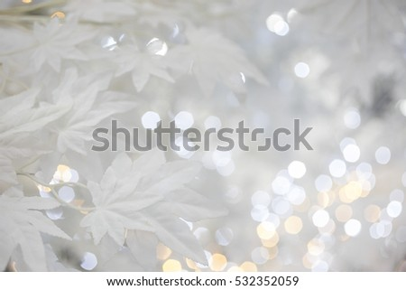 Christmas tree background with white artificial maple leaves