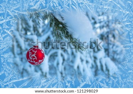 Christmas tree ball in the frozen window.  Fabulous background. - stock photo