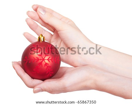 Christmas-tree ball lies on the woman's palm, while her other hand holds it by the cord. Showing the girls hands and Christmas tree decoration with a snowflake
