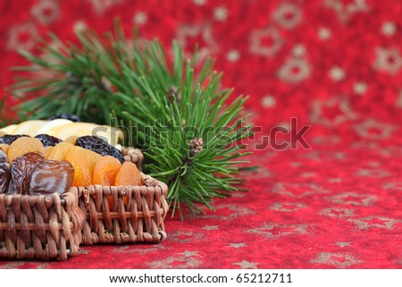 Christmas tree basket with dried fruits on red background. Shallow dof - stock photo