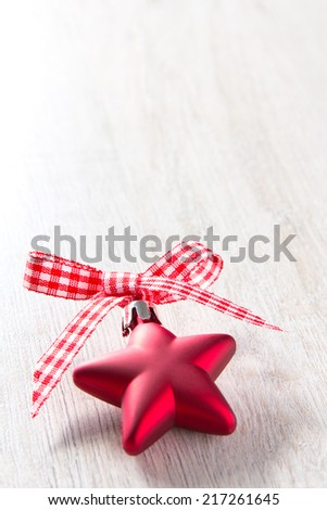 Christmas tree bauble in shape of a star with red and white ribbon in a bow on light wood, copy space - stock photo