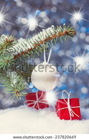 Christmas tree branch and decoration on abstract background with star luminous effect, shallow DOF focus on white ball - stock photo