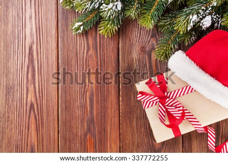 Christmas tree branch and santa hat with gift box on wooden table. Top view with copy space - stock photo
