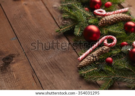 Christmas tree branch, candy, cones, balls on the background of wood