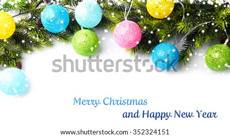 Christmas tree branch decorated with colourful lights on white background