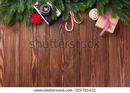 Christmas tree branch, gift box and camera on wooden table. Top view with copy space - stock photo