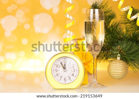 Christmas-tree branch, glass of champagne, gift box and about twelve hours - stock photo