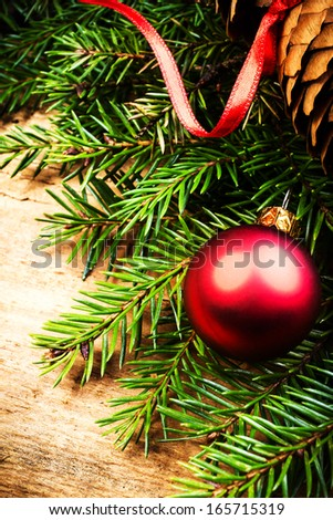 Christmas  Tree Branch on wooden background with festive ribbon and red ball . Christmas ornaments close up. Christmas Card. - stock photo
