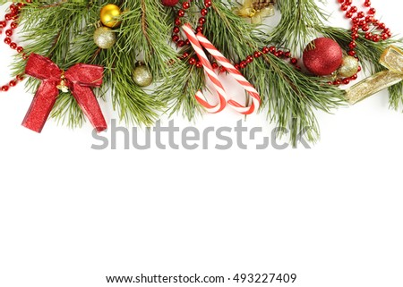 Christmas tree branch with baubles, candies on white background