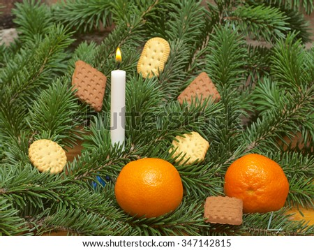 Christmas tree branch with burning candle and cookies and tangerines close up. - stock photo