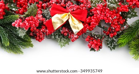 Christmas tree branch with red berries and bows on white background - stock photo