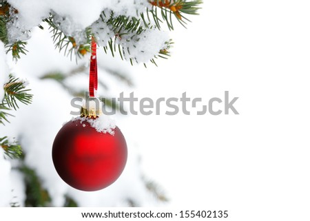 christmas tree branch with snow and ornament - stock photo