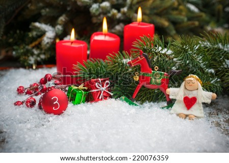 Christmas tree branches and candle for advent season three advent candles burning - stock photo