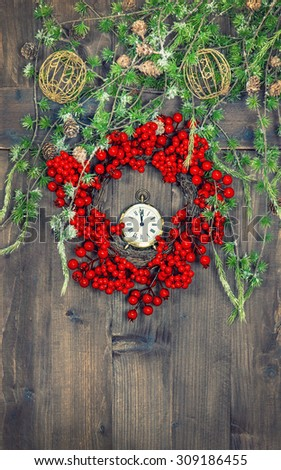 Christmas tree branches and wreath from red berries over rustic wooden background. Festive decoration. Vintage style toned picture - stock photo