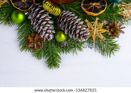 Christmas tree branches, dried oranges and fir and pine cones. Christmas greeting background with green balls and rustic ornaments. Copy space.