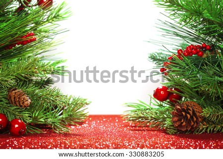 Christmas tree branches on glittering red background - stock photo