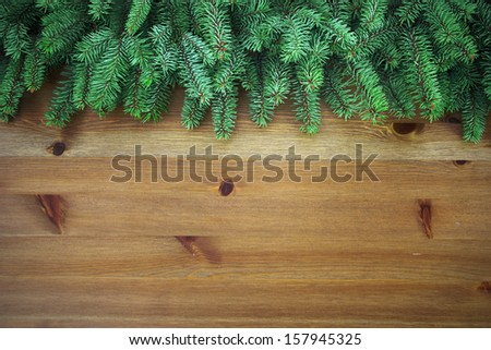 christmas tree branches over wooden board - stock photo