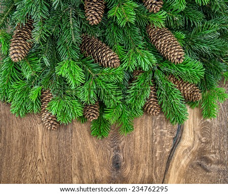 christmas tree branches with cones on wooden background. green border from undecorated evergreen twigs - stock photo