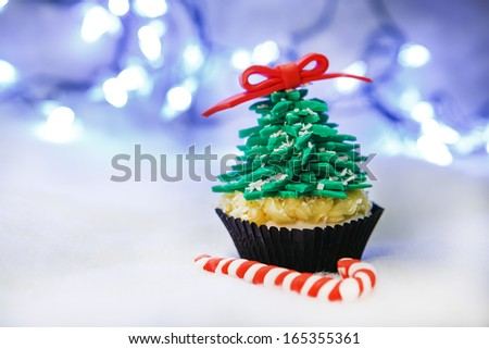 Christmas tree cupcake with white fondant with candy - stock photo