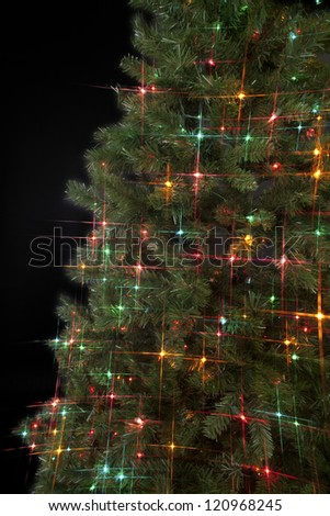 Christmas tree decorated with Christmas lights over dark background. - stock photo