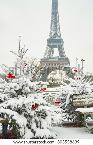 Christmas tree decorated with red balls and covered with snow on a rare snowy day in Paris. Eiffel tower is in the background - stock photo