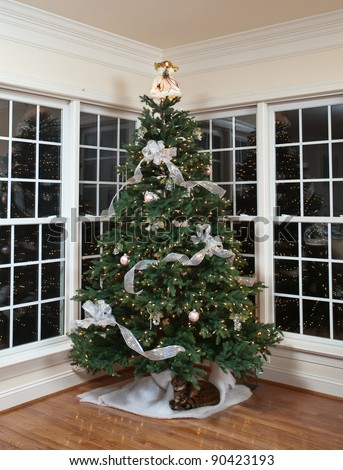 Christmas tree decorated with silver and white ribbons and ornaments in family home - stock photo