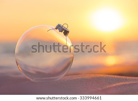 Christmas-tree decoration glass ball at sunset time ocean beach - xmas and New Year's vacation in hot countries concept - stock photo