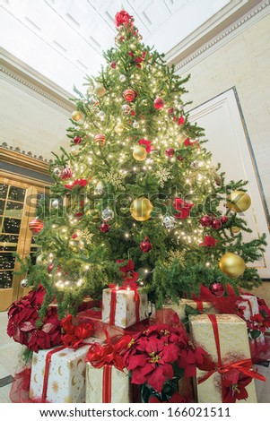 Christmas Tree Decoration with Bokeh Lights Ornaments Ribbons Poinsettia and Presents Under the Tree Tall Perspective