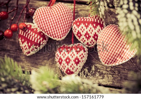 Christmas tree decorations hanging on branch against wooden background. Winter holidays concept. Shallow depth of fields - stock photo