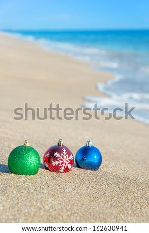 Christmas tree decorations on sea coast against wave - stock photo