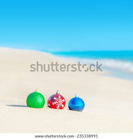 Christmas tree decorations on sea coast against wave - new years holiday in hot countries concept - stock photo