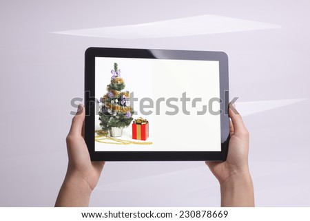 Christmas tree depicted on the tablet in hands - stock photo
