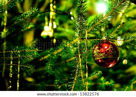 christmas tree detail with red christmas bauble and golden tinsel