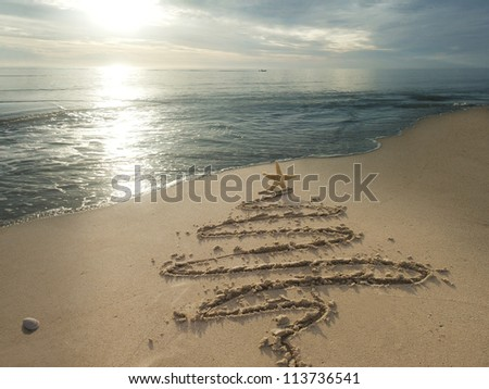 Christmas tree drawn in sand at the beach. Holiday concept. - stock photo