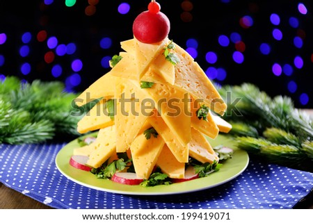 Christmas tree from cheese on table on dark background - stock photo