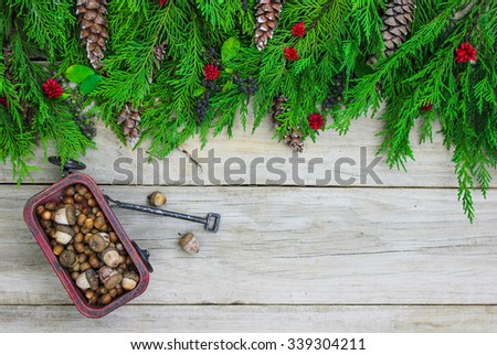 Christmas tree garland border with red wagon carrying acorns on antique rustic wooden background - stock photo