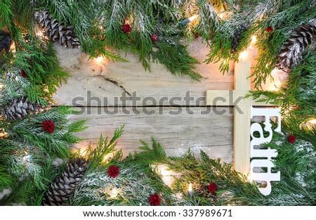 Christmas tree garland border with snow, lights, cross and the word Faith on antique rustic wooden background - stock photo