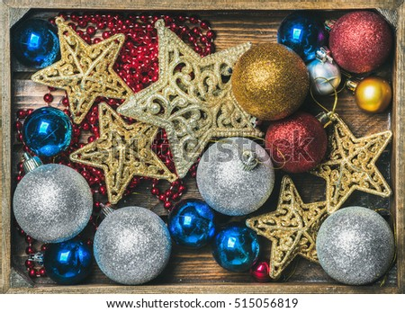 Christmas tree glittering toy stars, colorful balls and garland in wooden box, top view, horizontal composition