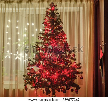Christmas tree in a dark living room with colored ornaments and red shinny lights, star lights at window and hanging Santa sox.